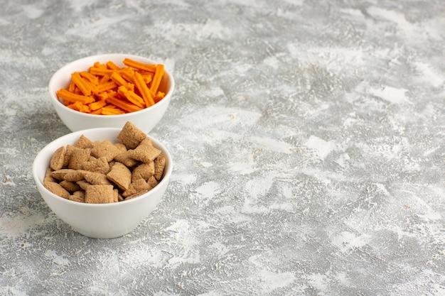 Orange zwieback der vorderansicht mit kissenplätzchen auf dem weißen schreibtisch