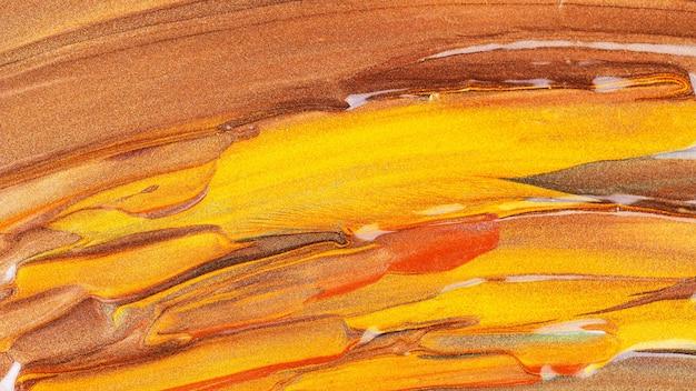 Orangebrauner hintergrund mit glitzernden abstrichen. abstrakte farbtextur. kreative pinselstriche aus goldfarbe. make-up-konzept. festliche kulisse