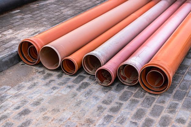 Orangefarbene abwasserrohre liegen auf einer baustelle. vorbereitung für erdarbeiten für die installation einer unterirdischen rohrleitung.