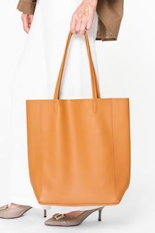 Orangefarbene damen-tragetasche aus leder mit designfläche