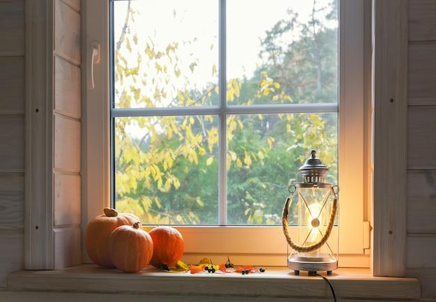 Orangefarbene kürbisse auf der fensterbank, kerzen, herbstblätter, laterne.