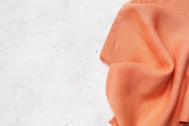 Orangefarbene serviette auf der rechten seite des abstrakten hintergrunds mit kopienraum, lebensmittelhintergrund