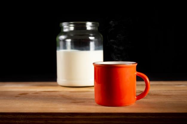 Orangefarbene tasse mit milchglas am boden. schwarzer hintergrund.