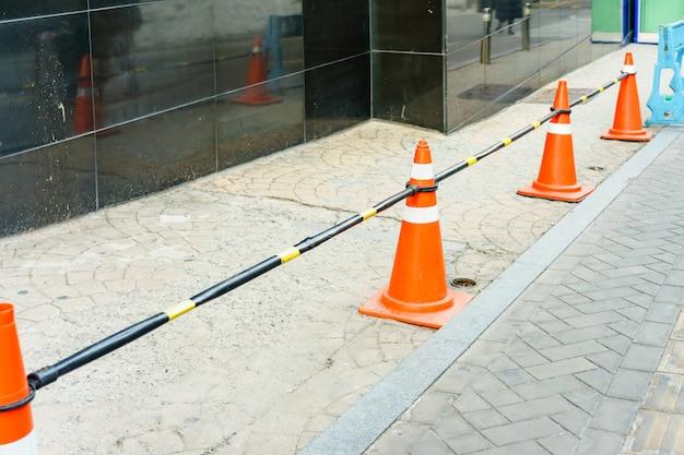 Orangefarbene verkehrskegel schützen die gefahren beim fahren oder im landverkehr, um die sicherheit zu gewährleisten.