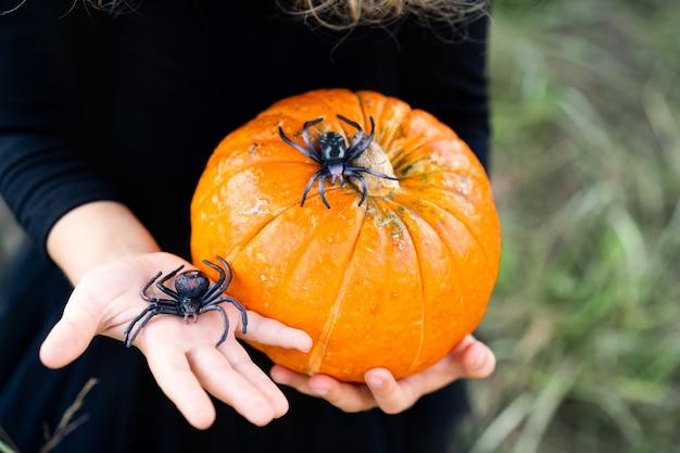 Orangefarbener herbstkürbis in kinderhänden mit spinnen, dekor für den halloween-urlaub.