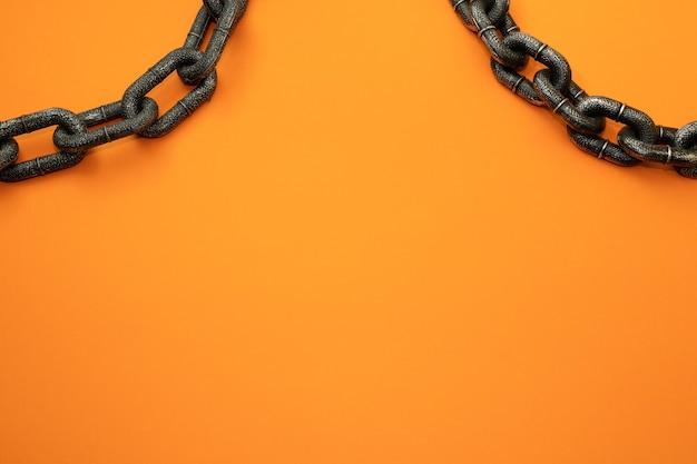 Orangefarbener hintergrund mit metallketten und einem kopierraum