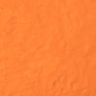 Orangefarbener lehm strukturierter hintergrund bunter handgemachter kreativer kunstzusammenfassungsstil
