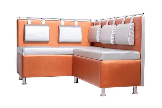 Orangefarbenes leder-bürosofa mit kissen und verchromten metallbeinen isoliert auf weiß