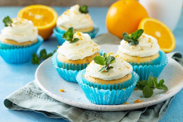 Orangen-cupcakes mit quarkcreme auf dem weihnachtsfesttisch