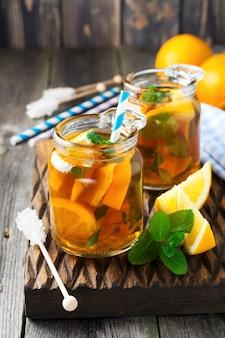 Orangen-eistee mit minzblättern in einem glas auf der alten holzoberfläche