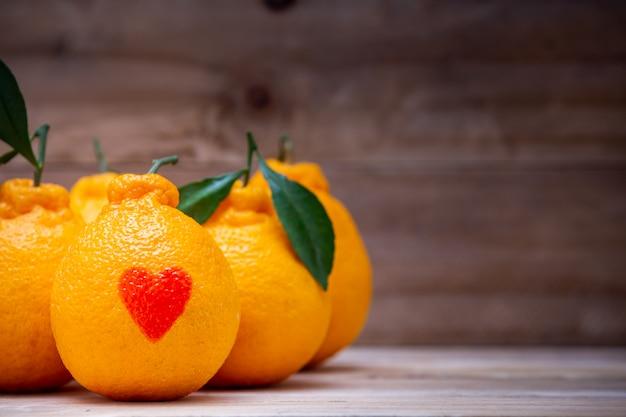 Orangen haben eine rote herzförmige auflage auf dem holztisch.