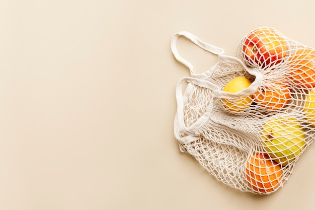 Orangen im netzbeutel mit designfläche auf beigem hintergrund