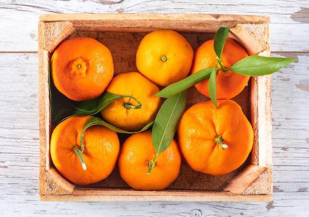 Orangen in der draufsicht des hölzernen kastens über weißen holztisch