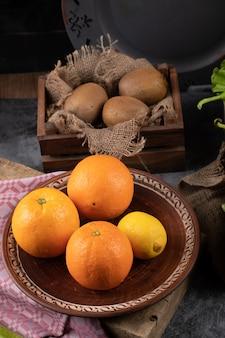 Orangen in einer platte und kiwies in einem rustikalen tablett.