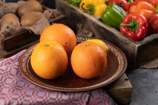 Orangen in einer platte und paprika herum