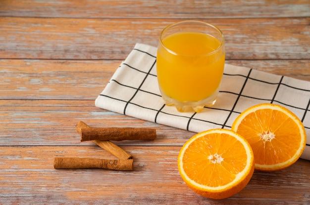 Orangen in scheiben geschnitten und mit einer tasse saft und zimtstangen serviert
