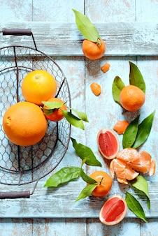 Orangen, mandarinen, grapefruit mit blättern und zweigen eines weihnachtsbaumes, kranz. weihnachten, neujahr, konzept, kopierraum.