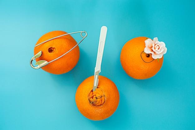 Orangen mit großem und kleinem nabel, nadel, skalpell und blüte. konzept zur behandlung und vorbeugung von hämorrhoiden.