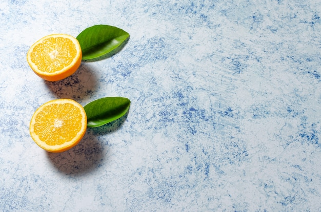 Orangen mit ihren blättern auf einem blauen hintergrund