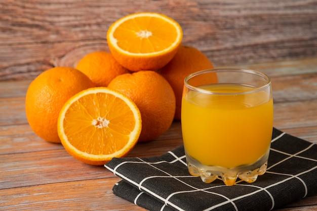 Orangen und ein glas saft auf einem schwarzen küchentuch