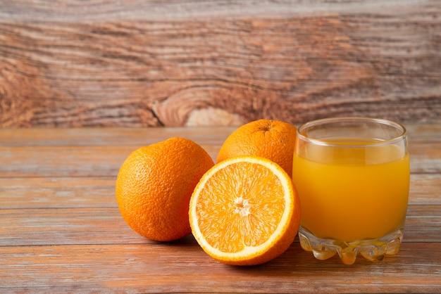 Orangen und ein glas saft isoliert auf holz