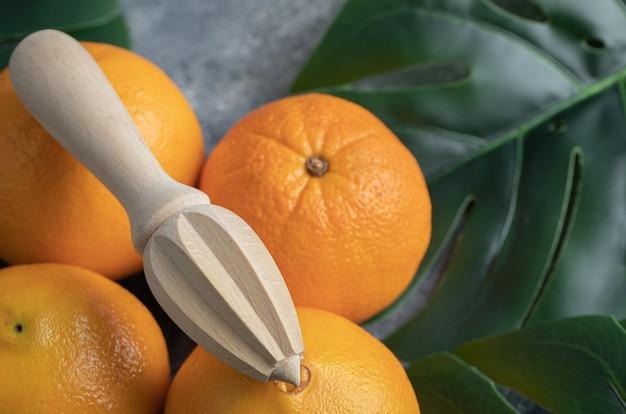 Orangen und hölzerne reibahle auf marmortisch.