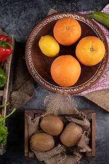 Orangen und kiwies in rustikalen platten.