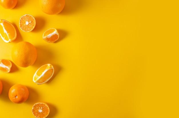 Orangen und mandarinen ganz und auf hellgelbem grund in stücke geschnitten. draufsicht, flache lage, kopierraum, minimalistisches konzept