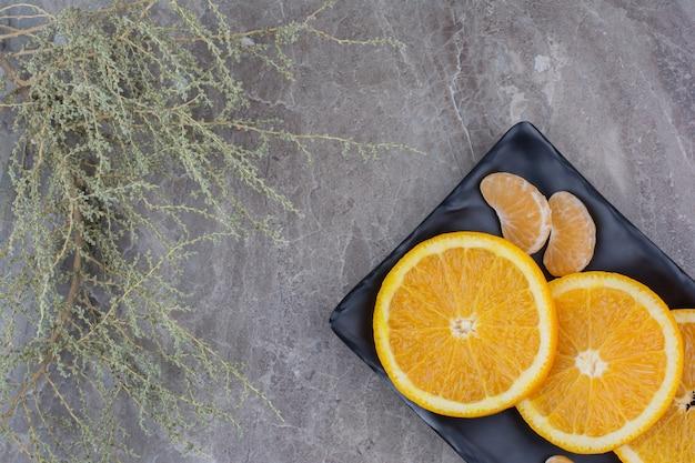 Orangen- und mandarinenscheiben auf schwarzem teller.
