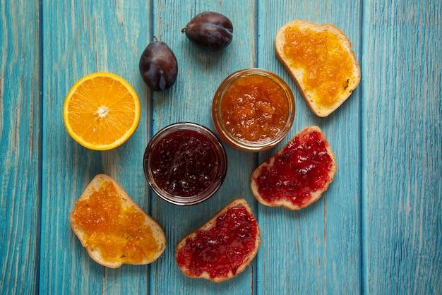 Orangen- und pflaumenkonfektion in einem glas und auf dem toastbrot.