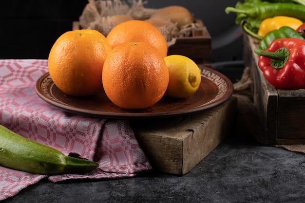 Orangen und zitrone auf einer platte auf einem stück stein.