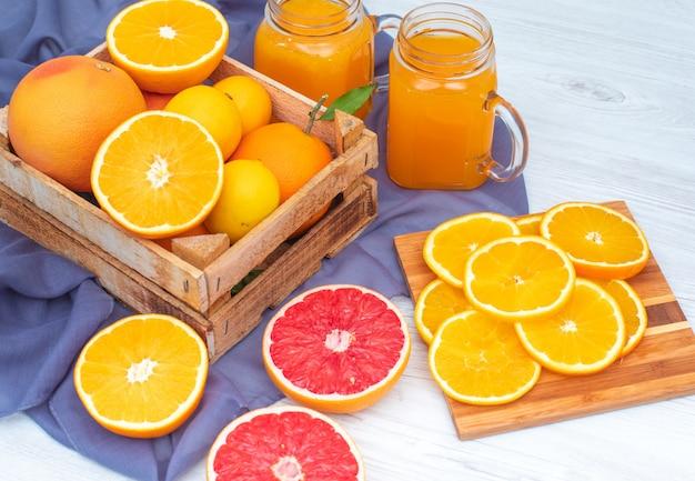 Orangen und zitronen in der holzkiste vor gläsern orangensaft auf violettem stoff