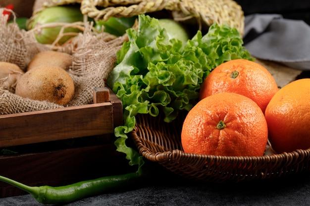 Orangen und zitronen mit salatblättern in einem rustikalen