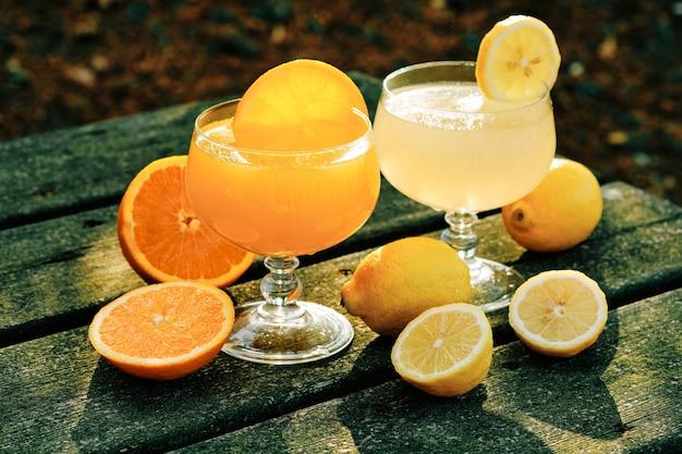 Orangen- und zitronensäfte in der glasschale auf rustikalem tisch im park