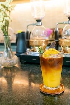 Orangen- und zitronensaft-soda mit schwarzem kaffee in glas mit rosmarin und zimt