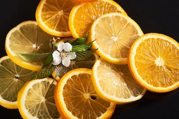 Orangen- und zitronenscheiben, isoliert auf einem schwarzen.