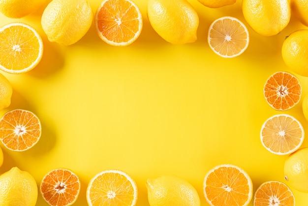 Orangen, zitrone auf pastellgelbem papier, kopierraum.