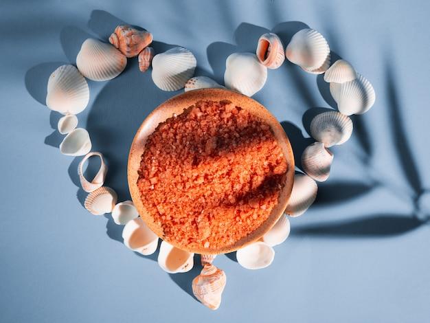 Orangenbadesalz in einer untertasse mit muscheln auf einem blauen hintergrund mit einem schatten von einer tropischen pflanze. copyspace, flatlay. spa, entspannt, sommer
