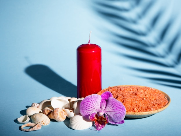 Orangenbadesalz in einer untertasse mit muscheln, roter kerze und blume auf einem blauen hintergrund mit einem schatten von einer tropischen pflanze. copyspace. spa, entspannt, sommer