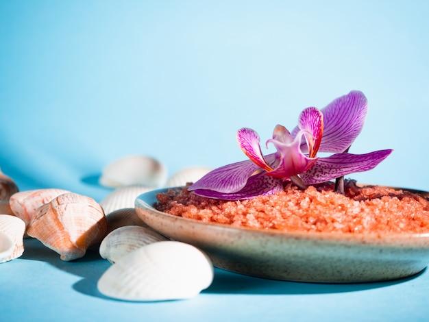 Orangenbadesalz in einer untertasse mit muscheln und blume auf einem blauen hintergrund mit einem schatten von einer tropischen pflanze. copyspace. spa, entspannt, sommer