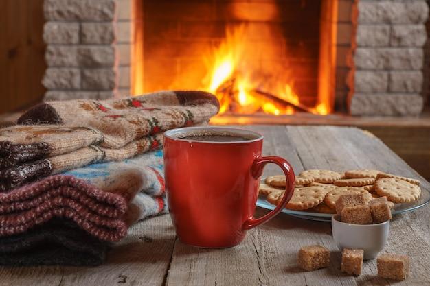 Orangenbecher für tee oder kaffee; wollsachen in der nähe eines gemütlichen kamins.