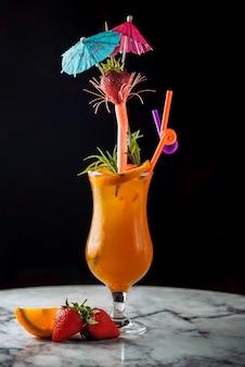 Orangencocktail des sommergetränks mit rohren und regenschirmen.