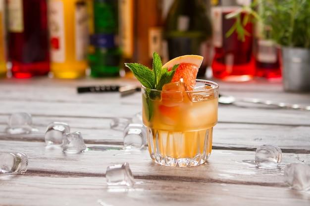 Orangencocktail im glas. grapefruitscheibe und eiswürfel. originelles alkoholisches getränk. berechnen sie die zutaten sorgfältig.