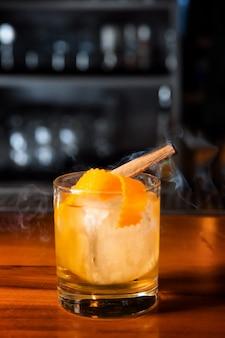 Orangencocktail mit eiswürfel und orangenschale, im glas befindet sich eine zimtstange, aus der rauch entsteht