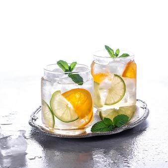 Orangencocktail mit minze und limette. kaltes erfrischungsgetränk oder getränk mit eis. kalte getränke mit eis und minze.