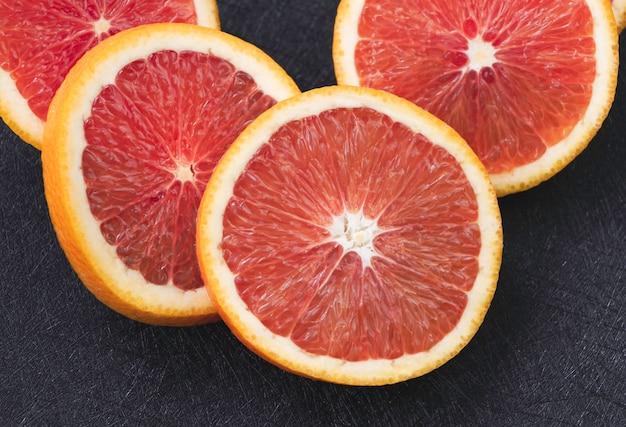 Orangenfrucht in scheiben geschnitten, rosa fruchtfleisch und gelbe schale zeigen, verschwommenes licht herum