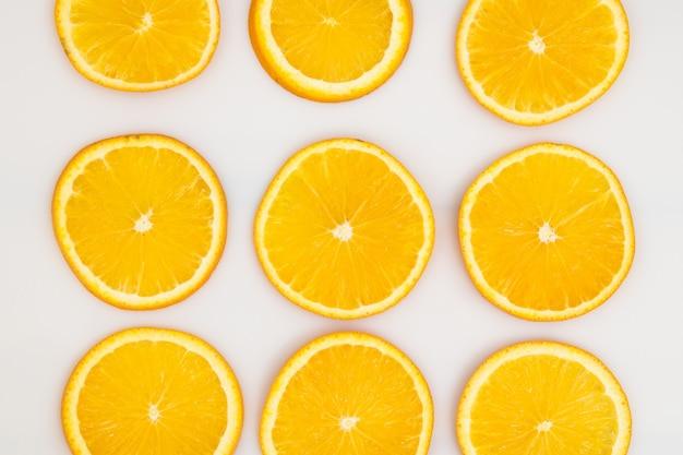 Orangenfrucht in scheiben schneiden und als muster auf weiß legen.