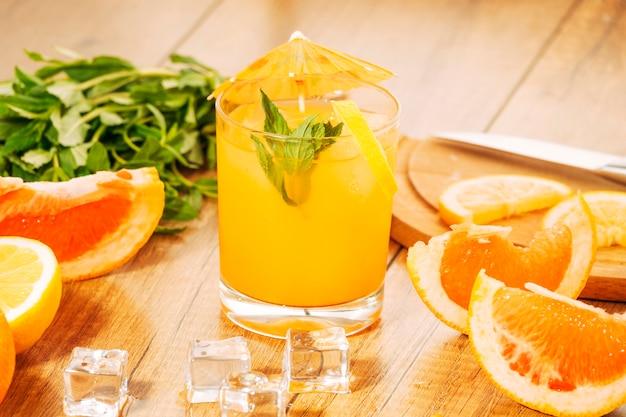 Orangenfrucht und saft mit regenschirm schneiden