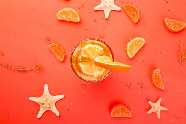 Orangenfruchtcocktail-entgiftungswasser auf orangefarbener oberfläche