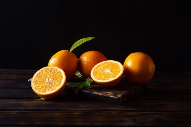 Orangenfrüchte ganz und geschnitten auf einem rustikalen holztisch